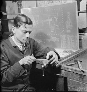 INDIAN ARMS WORKERS TRAIN IN BRITAIN: WAR INDUSTRY AT LETCHWORTH, HERTFORDSHIRE, ENGLAND, UK, 1941 (D 5932) A portrait of an Indian technican at work at the Government Training Centre, Letchworth. He appears to be filing a piece of metal at a workbench. Behind him can be seen a diagram of some kind of gear system, which features a list of component parts in the bottom right hand corner. Copyright: © IWM. Original Source: http://www.iwm.org.uk/collections/item/object/205125709